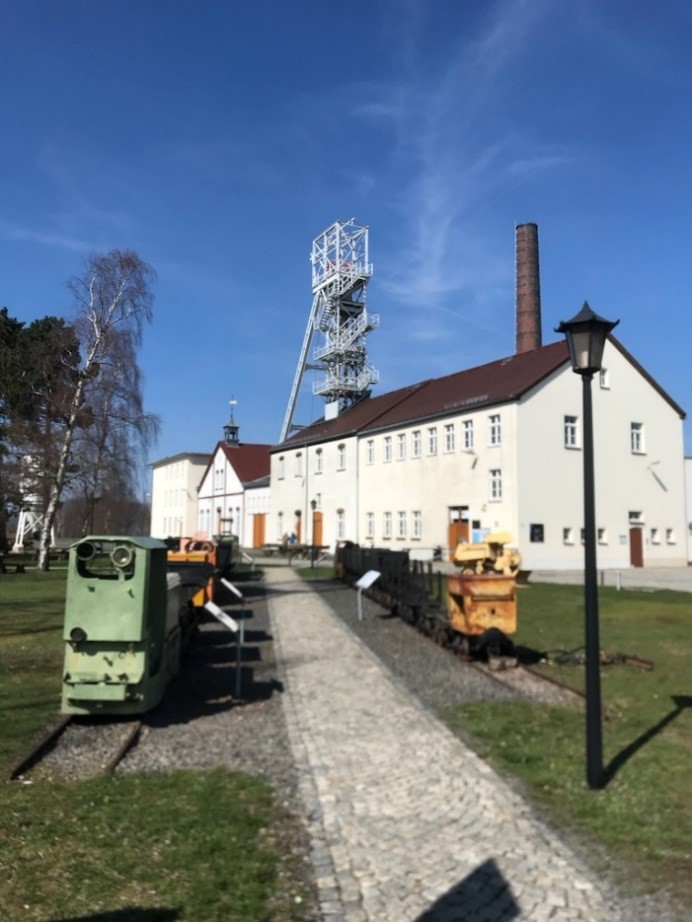 The Reiche Zeche mine building, with old mine equipment outside and the shaft tower visible